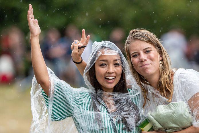 Festivalbezoekers dragen poncho's tegen de regen.