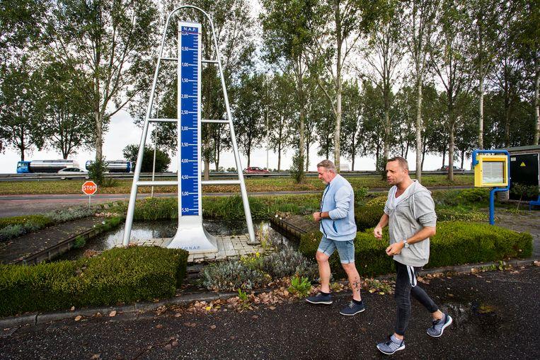Bewoners Rob van Lopik (links) en Eelko Doornhein bij het Monument laagste punt van Nederland in Nieuwerkerk aan den IJssel Beeld Arie Kievit