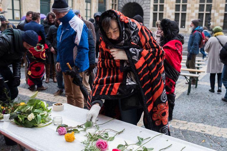 Een vrouw legt een bloem neer om de straatdoden van de stad te herdenken.