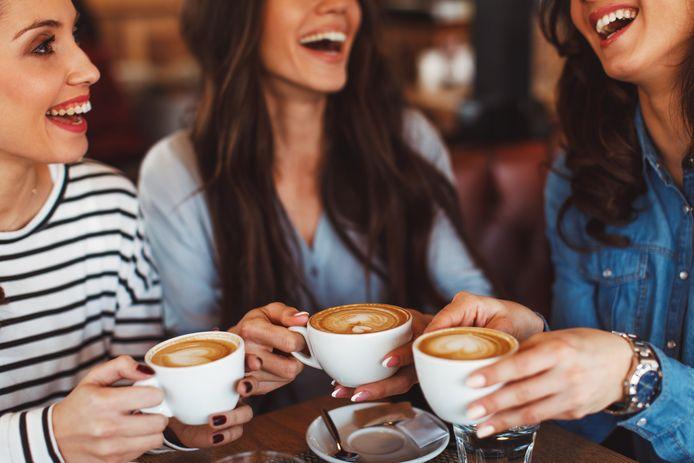 Drie jonge vrouwen drinken koffie.