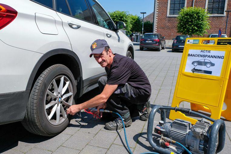 Illustratiebeeld - man controleert de bandenspanning van een wagen.
