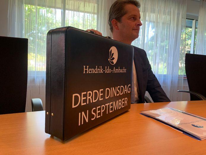 Wethouder André Flach van Hendrik-Ido-Ambacht met het koffertje waarin hij de begroting voor volgend jaar presenteerde.