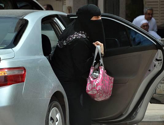 Een Soeidische vrouw stapt uit een auto nadat ze gebracht is door een chauffeur.