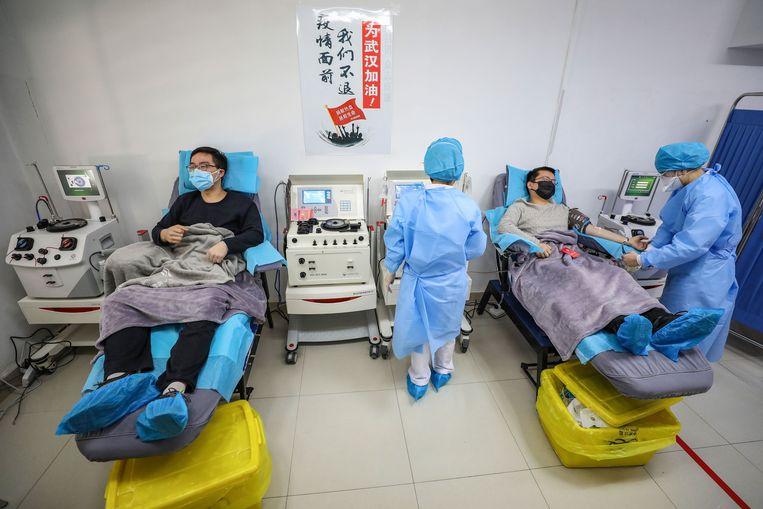 Patiënten die hersteld zijn van het coronacrisis doneren hun plasma in Wuhan, China.  Beeld AFP