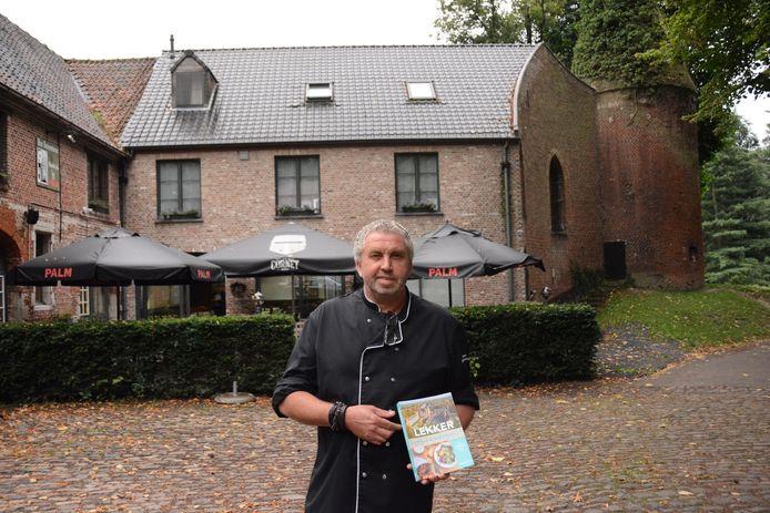 Eigenaar Dany Lagae met het restaurant en de aanpalende duiventoren op de achtergrond.