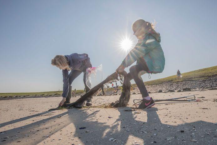 Kinderburgemeester Mares de Regt trekt een stuk plastic uit het strandje bij Wissenkerke. Haar moeder Yvette helpt een handje.