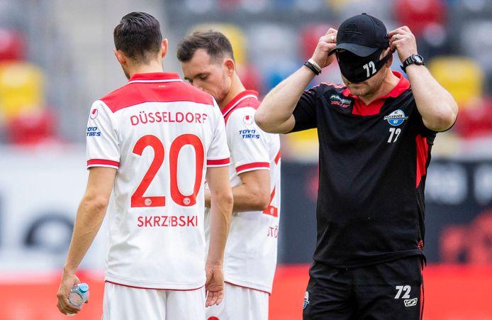 Paderborn-trainer Steffen Baumgart doet zijn mondmasker op. Het is trainers niet verplicht om met een mondmasker op langs het veld te staan.