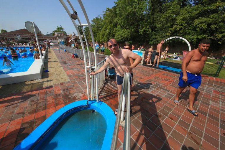 Steven Caulier bij een van de kapotte douches. Bemerk het vuile water.
