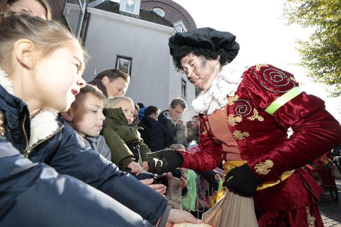 Kinderen krijgen kruidnoten van een roetveegpiet.