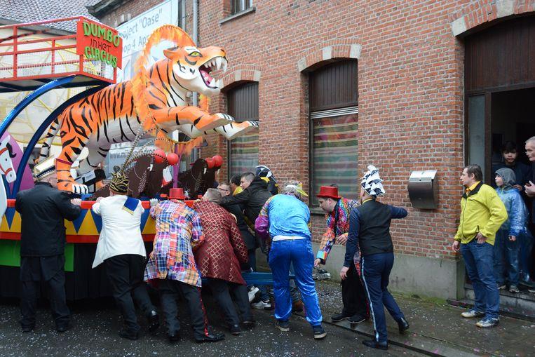 Carnavalisten snellen ter hulp om de wagen terug op het juiste spoor te krijgen.