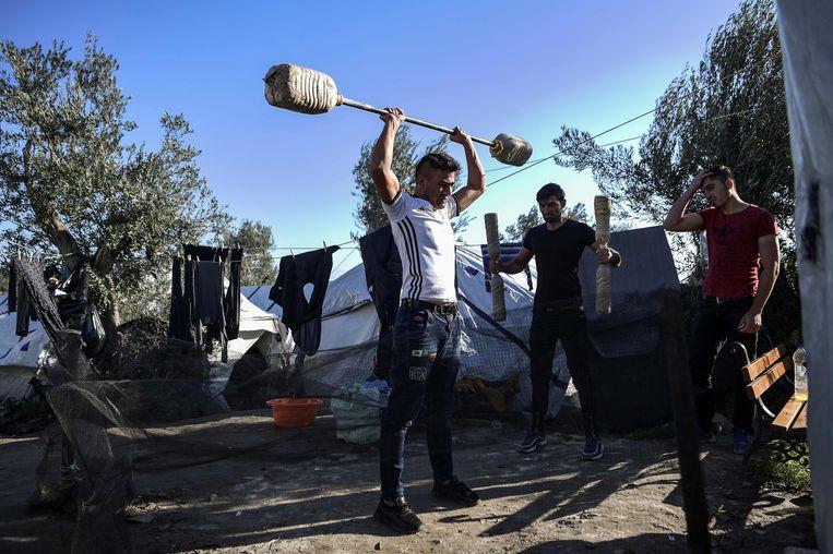 Jonge mannen trainen met zelfgemaakte gewichten in het opvangkamp Moria, op het eiland Lesbos. Beeld AFP