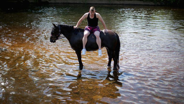 Een jongen rust uit tijdens de wasbeurt van zijn paard in de rivier Eden op het paardenfestijn in het Britse Appleby. Beeld getty