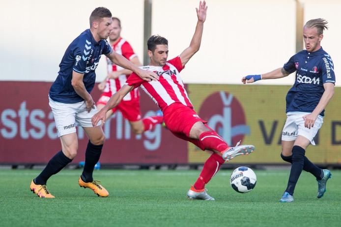 Fatih Kamaci (FC Oss) in duel met Jeroen Verkennis (links) en Jason Bourdouxhe van Helmond Sport.