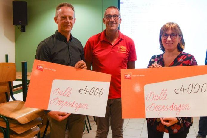 De organisatoren van Dulle Dorpsdagen overhandigen 8.000 euro aan basisschool Heikant en parochiezaal De Kring.