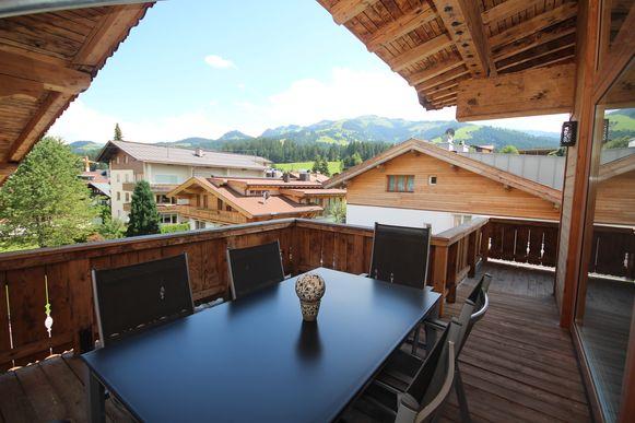 Vanop het terras van het duplexappartement kijk je uit op de bergen.