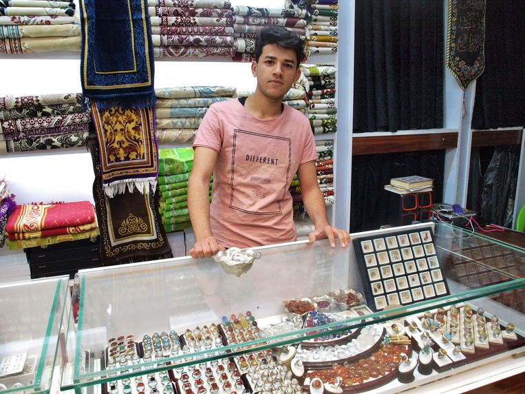 Ahmed Ali laat de witte stenen zien die populair zijn bij Iraanse pelgrims. Beeld Judit Neurink