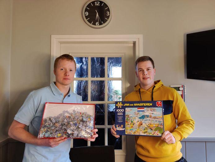 Twee deelnemers met de nog complete puzzel in de originele verpakking onder de klok aan het begin van het toernooi.