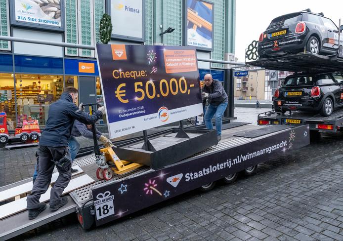 Medewerkers van de Staatsloterij laden het bord uit waarop het 'vermiste' lotnummer staat voor de prijs van een halve ton.