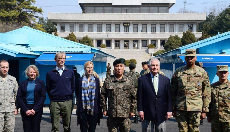 De nieuwe Amerikaanse minister van buitenlandse zaken Rex Tillerson (derde van rechts) poseert met Zuid-Koreaanse en Amerikaanse functionarissen in Panmunjom in de gedemilitariseerde zone tussen Zuid- en Noord-Korea. Het gebouw op de achtergrond is van Noord-Korea.  Beeld EPA