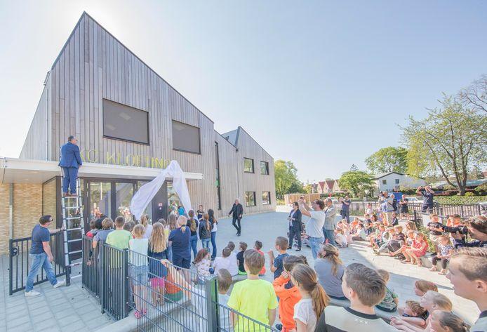 Het nieuwe schoolgebouw in Kloetinge heeft de naam 'IKC Kloetinge' gekregen. Wethouder André van der Reest (op de ladder) onthulde de naam woensdag.