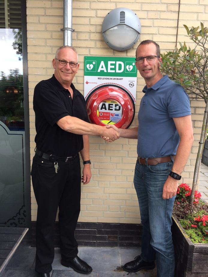 John Peters (links) van De Bongerd en Arien Boekhoudt van de EHBO-vereniging Heteren zijn blij met de nieuwe AED die door een bijdrage van Heteren Doet kon worden aangeschaft.