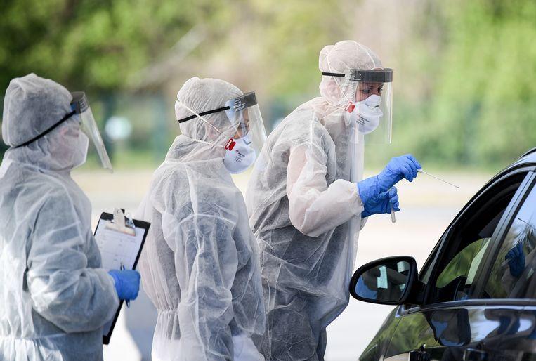 Gezondheidswerkers doen een swab-test bij een test-drive-in. Beeld DPA