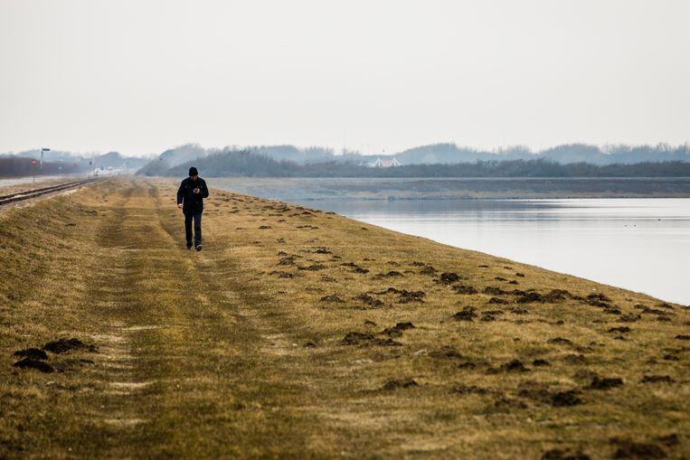 Een wandelaar bij de Brouwersdam bij het Grevelingenmeer. Het kabinet trekt geld uit voor een doorlaat in de dam, om de waterkwaliteit van het Grevelingenmeer te verbeteren. Beeld ANP