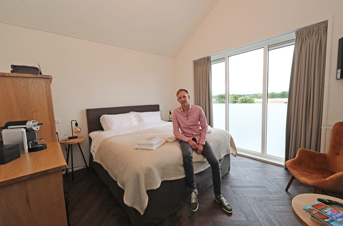 Paul Roebroek op bed in zijn nieuwe bed and breakfast. ,,Gasten kunnen uit vier verschillende kussens kiezen.''