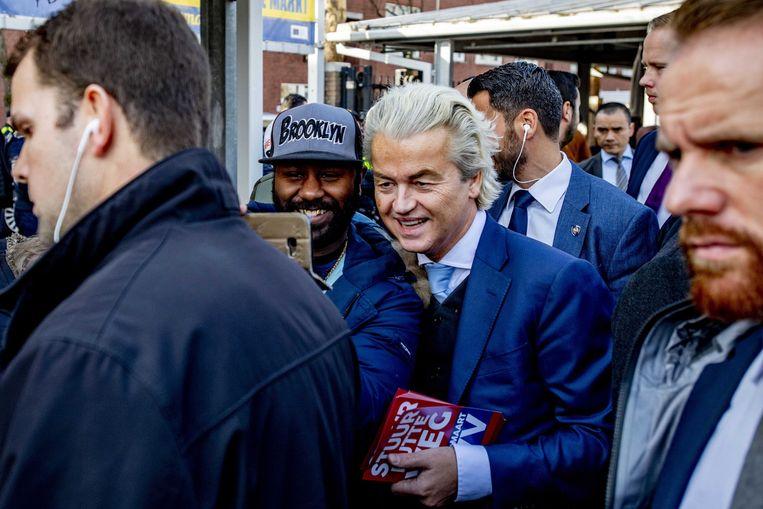 PVV-leider Geert Wilders, zaterdag 16 februari bij de aftrap van zijn verkiezingscampagne in Den Haag, laat zich tussen zijn beveiligers in fotograferen door een bezoeker van de Haagse markt. Beeld EPA