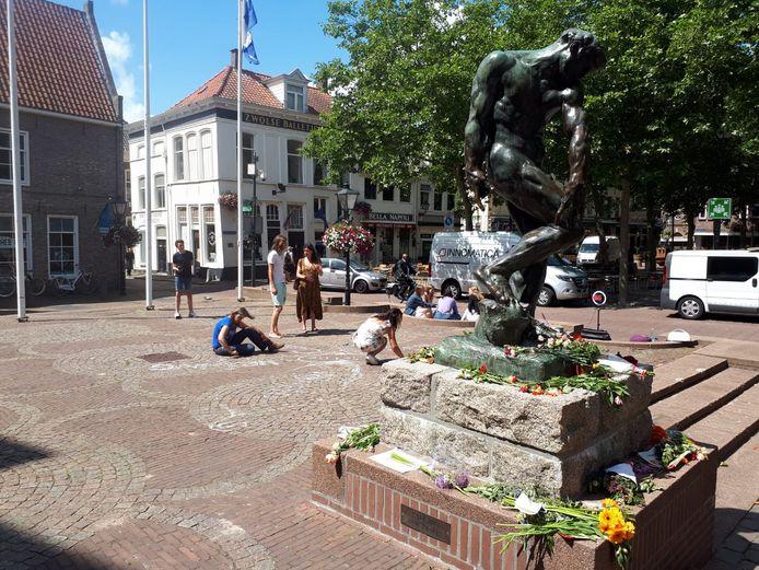 Voor het stadhuis in Zwolle tekenen de actievoerders een grote bloem. Bij het standbeeld werden zondag tientallen bloemen en protestbrieven gelegd.
