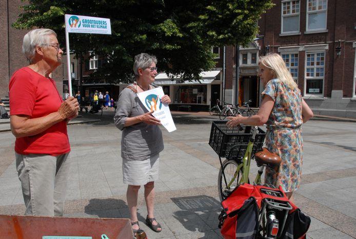 Leden van de beweging Grootouders voor het Klimaat in gesprek met Mieke van den Broek, een van de passanten op het Kerkplein