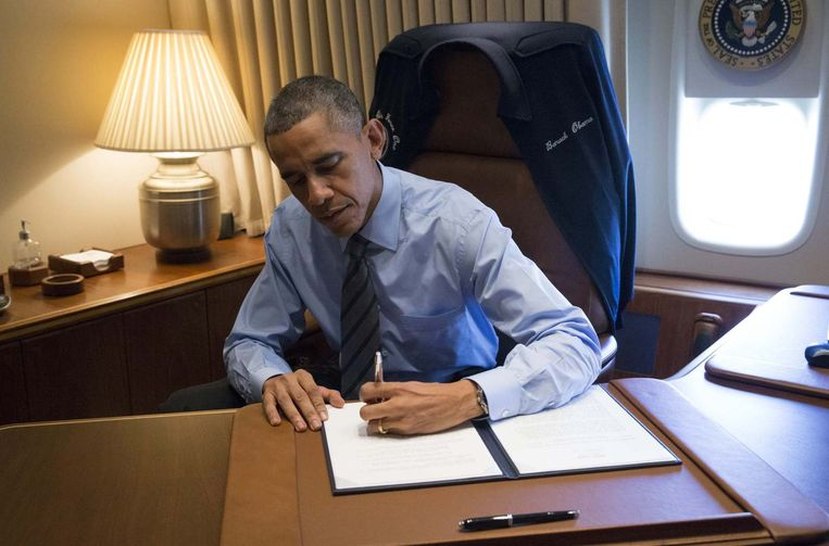 Obama tekent de nieuwe immigratiemaatregelen aan boord van de Air Force One. Beeld reuters