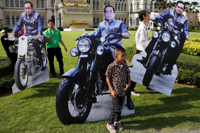 Thaise ambtenaren lopen met verschillende sportieve versies van de minister-president onder hun arm. Vandaag was het Nationale kinderdag en mochten kinderen bij het parlementsgebouw met de kartonnen premier op de foto. Foto Athit Perawongmetha