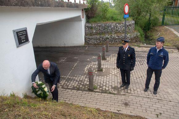 Zonechef Gerritjan Maes, burgemeester Alain Pardaen en brandweerluitenant Walter Frulleux leggen bloemen neer aan de herdenkingsplaat voor de treinramp in Wetteren.