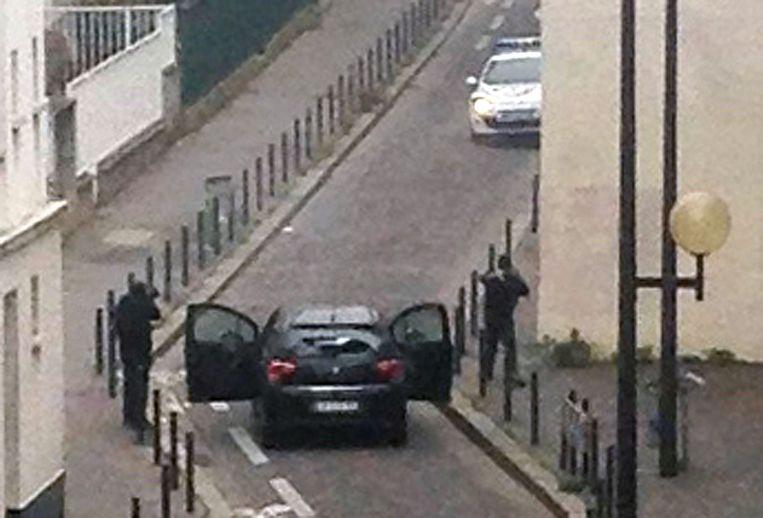 7 januari 2015: de Algerijns-Franse broers Kouachi schieten in een straat in Parijs op een politieauto na hun aanval op de redactie van het satirische weekblad Charlie Hebdo. Beeld AFP