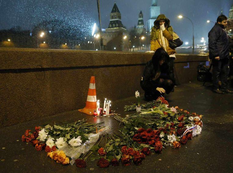 Mensen laten bloemen en kaarsen achter op de plek waar Boris Nemtsov gisteren vermoord werd.