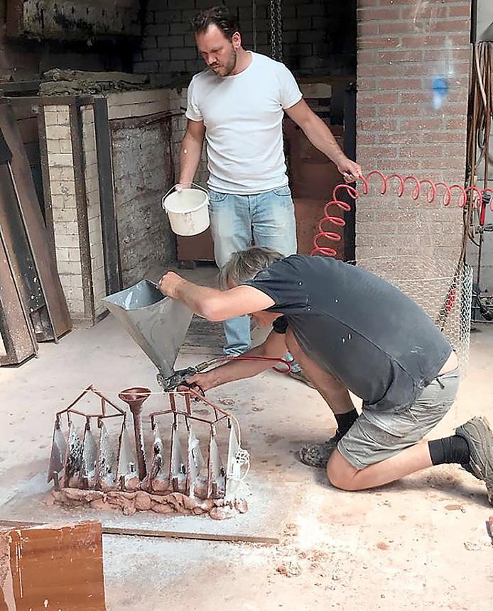 Léon Vermunt (zittend) en Ruben Van de Ven bezig met het maken van de eerste gietmallen voor het kunstwerk d' Ouwe Sok van Roosendaal.