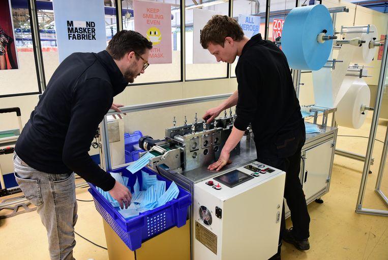 De mondkapjesmachine wordt afgesteld. Beeld Marcel van den Bergh / de Volkskrant