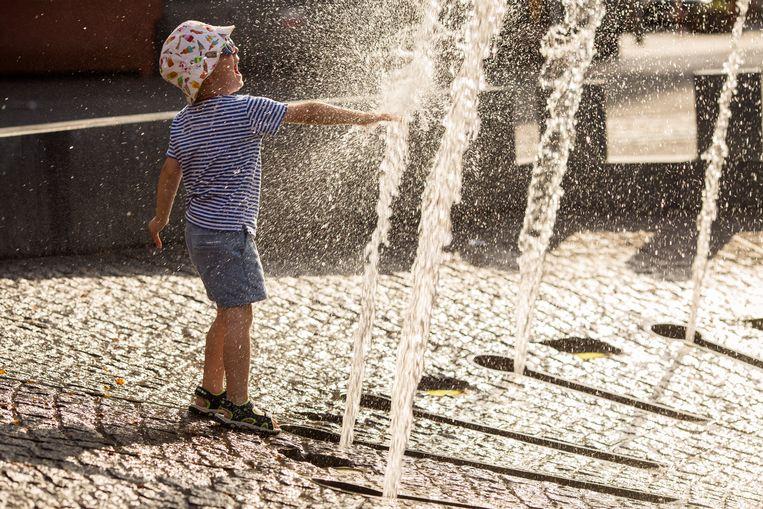 Een kind speelt in het water van de fontein op de Grote Markt van Ieper tijdens de warmste dag ooit.