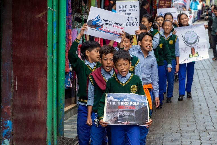 Tibetaanse schoolkinderen in ballingschap gingen eerder vandaag in Dharmsala, India, de straat op voor het klimaat. Beeld AP