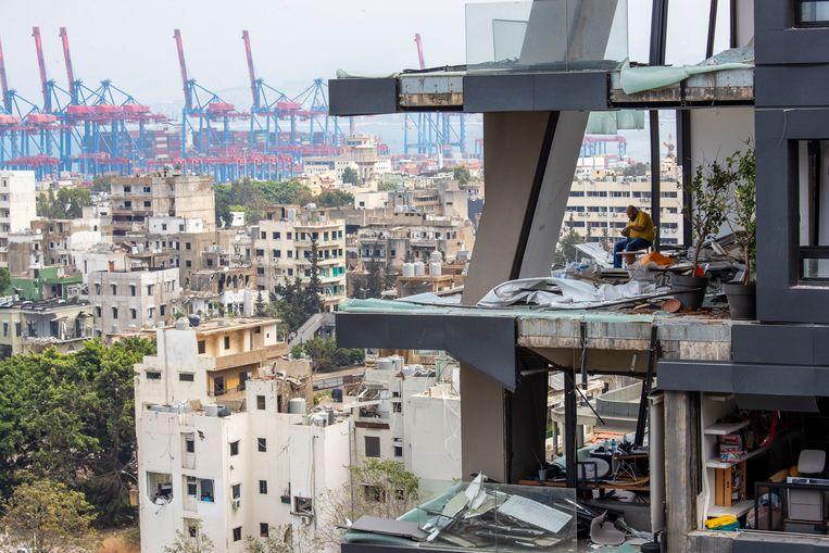 Een man zit tussen het puin in zijn huis in Beiroet. Beeld AP