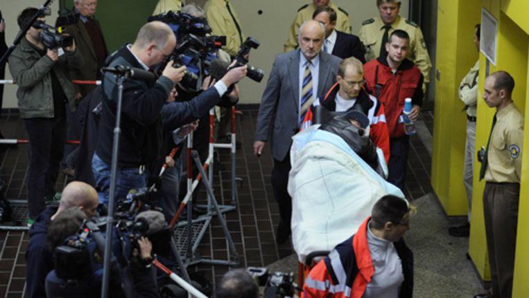 Demjanjuk, met baseballpetje, wordt tijdens een pauze in de rechtzaak weggereden. Foto AP Beeld