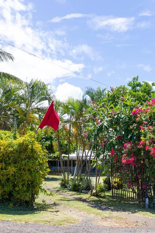 Een rode vlag bij een huis van Apia.