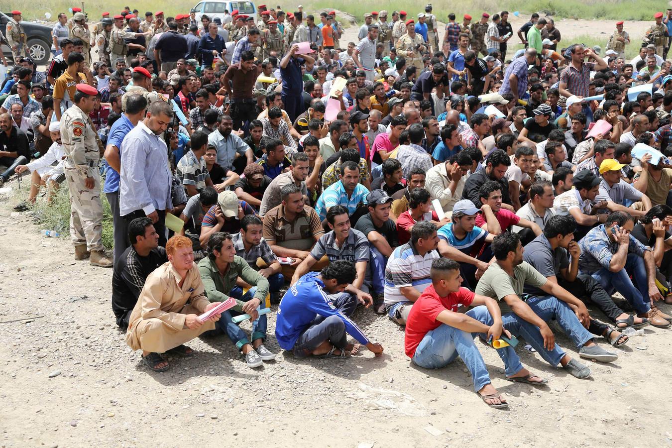 Irakese mannen verzamelen zich om zich te laten rekruteren voor het leger om te helpen vechten.