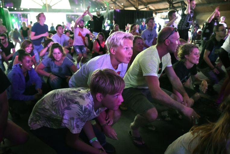 Publiek moet op de hurken bij een optreden van een muziekgroep. Beeld Marcel van den Bergh