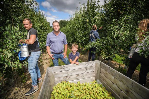 Fruitteler Raf Goffin (midden) met zoontje Matteo en enkele Poolse werkstudenten.