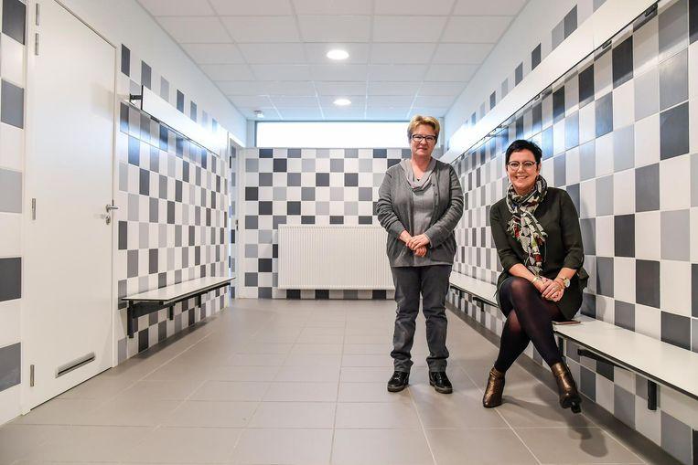 Schepenen Leen Dierick en Carine Verhelst in de vernieuwde kleedkamer in de sporthal van Oudegem.