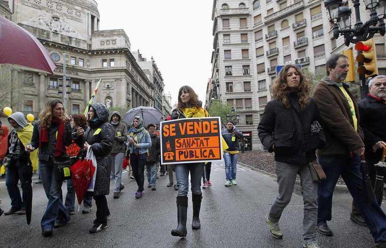 Betoging in Barcelona, afgelopen zondag. 'Te koop: gezondheidszorg' staat op het bord. Beeld reuters