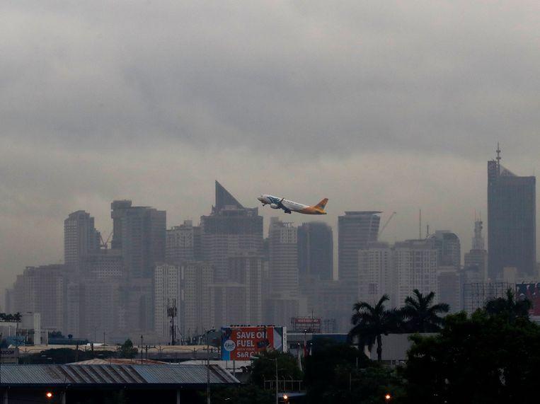 Een vliegtuig stijgt op boven Makati City in de Filipijnen.