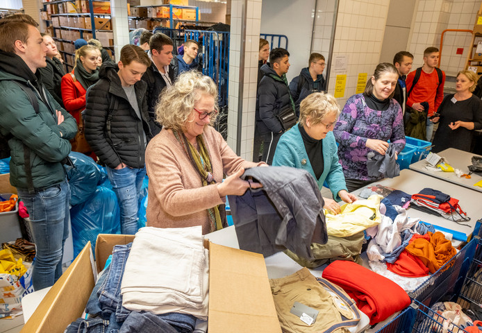 Studenten van de HZ krijgen een rondleiding in het sorteercentrum van de Kledingbank Zeeland. Lenny Krijger (rechts) vertelt hoeveel kleding er binnenkomt, wordt uitgezocht en wordt verstrekt aan mensen in armoede.